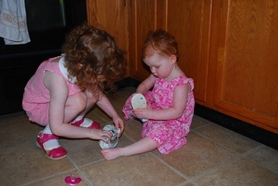 #1 helps put #2's shoes on.