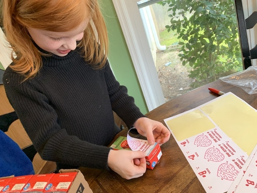 attaching valentine stickers to juice boxes
