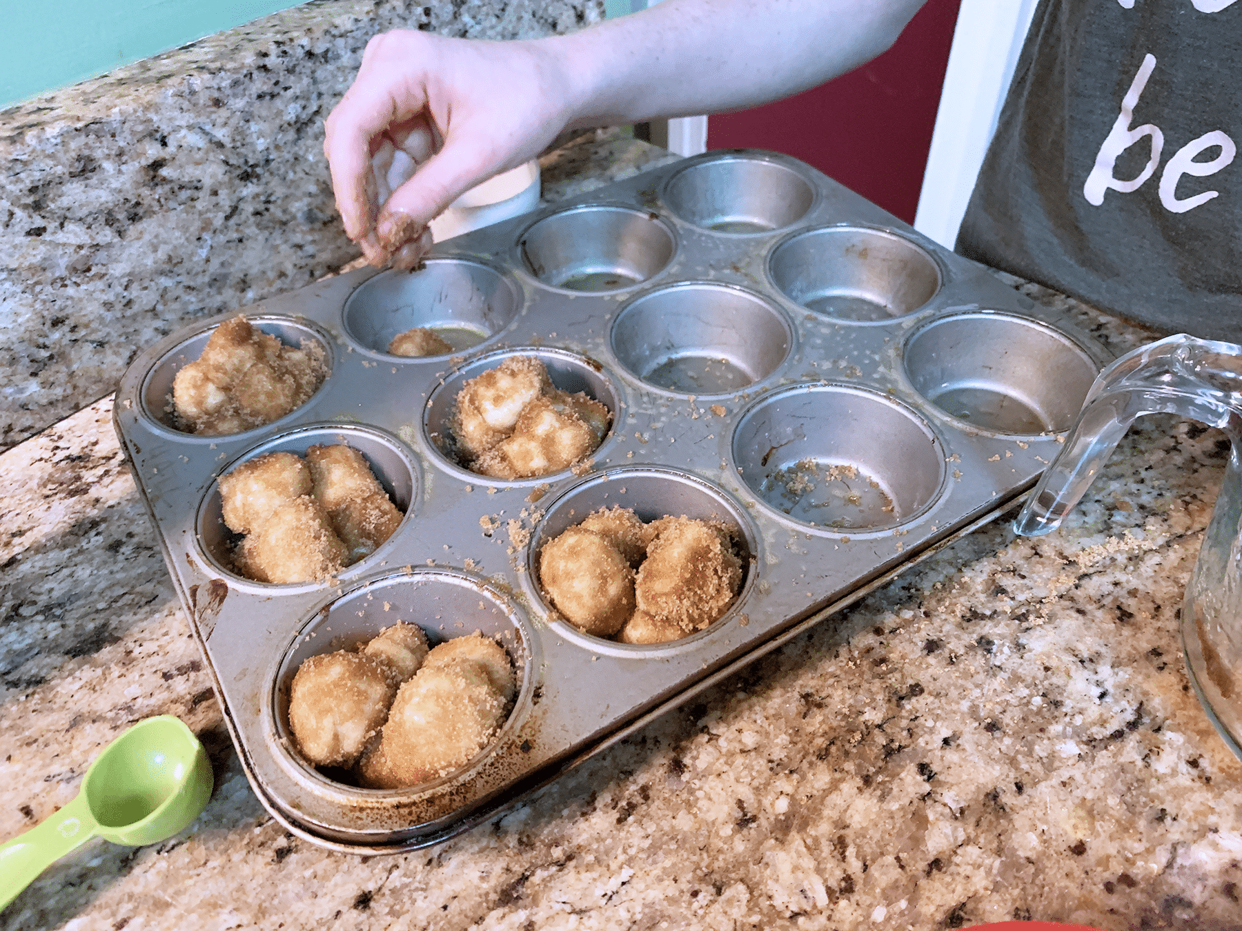 putting monkey bread into muffin tin copy
